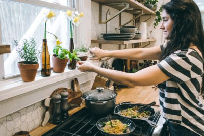 increasing efficiency | an image showing a woman cooking and clipping herbs